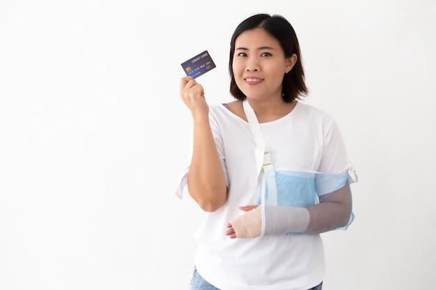 Die asiatin, die kreditkarte hält und setzte an eine weiche schiene Premium Fotos