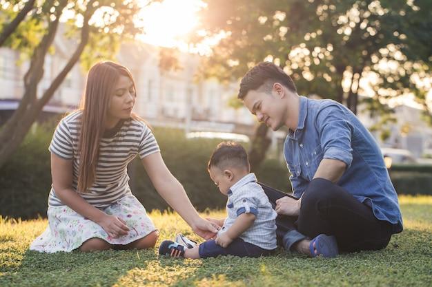 Die asiatische familie, die im garten sitzt, mamma und vati kümmern sich um ihren sohn auf dem rasen Premium Fotos