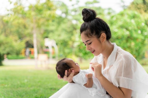 Die asiatische junge schöne mutter, die sie neugeboren hält, schläft und glaubt mit liebe und berührt leicht dann das sitzen auf grünem gras im park Premium Fotos
