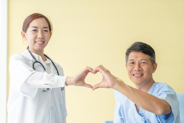 Die asiatische lächelnde ärztin und lassen herz mit älterem patienten eigenhändig rasieren Premium Fotos