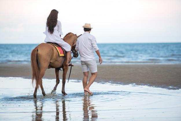 Die asiatische reisende frau, die ein pferd reitet und mach's gut mit seinem freund am seestrand. Premium Fotos