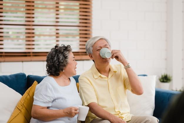 Die asiatischen älteren paare, die warmen kaffee trinken und zu hause im wohnzimmer zusammen sprechen, paare genießen liebesmoment beim auf sofa liegend, wenn sie zu hause entspannt werden. Kostenlose Fotos