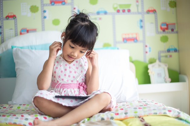 Die asiatischen kinder, die kopfhörer für verwenden, hören musik durch smartphone auf dem bett in ihrem verzierten schlafzimmer Premium Fotos