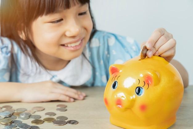 Die asiatischen mädchen lassen gerne das sparschwein fallen, um mit der weißen wand geld zu sparen. geld sparen konzept. Premium Fotos