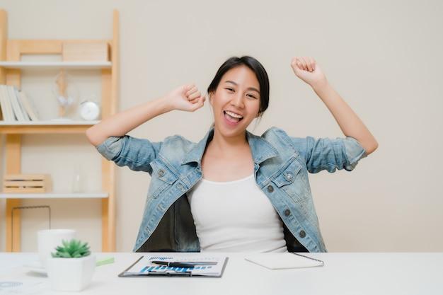 Die asien-geschäftsfrauerfolgsfeier, die arme hält, hob zu hause büro an. Kostenlose Fotos