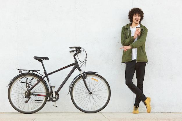 Die atelieraufnahme des jungen mannes mit dem gelockten haar, gekleidet im modernen anorak, zeigt mit dem zeigefinger auf fahrrad, annonciert neues modell, trinkt mitnehmerkaffee, trifft die wahl, lokalisiert auf weißem hintergrund. Premium Fotos