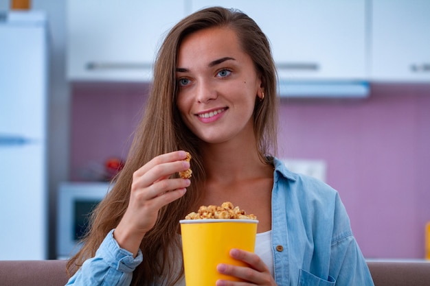 Die attraktive frau des glücklichen lächelns, die sich ausruht und knuspriges karamellpopcorn isst, während sie comedy-film zu hause ansehen. popcorn-film Premium Fotos