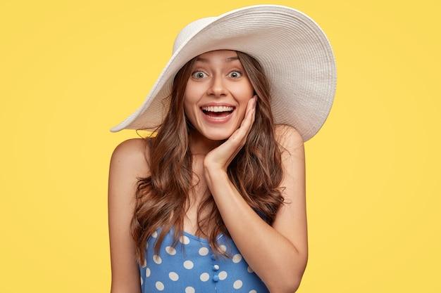 Die aufnahme einer begeisterten lächelnden jungen dame hat natürliches dunkles haar, weiße zähne, ein breites lächeln, berührt die wange mit der hand, trägt einen stilvollen sommerhut, ist begeistert von großartigen neuigkeiten und isoliert über der gelben wand Kostenlose Fotos