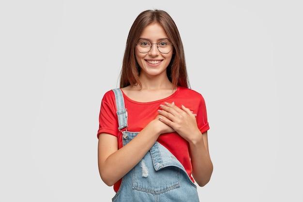 Die aufnahme einer erfreuten, freundlichen dame hält die hände auf brust oder herz und wird von positiven worten bewegt Kostenlose Fotos