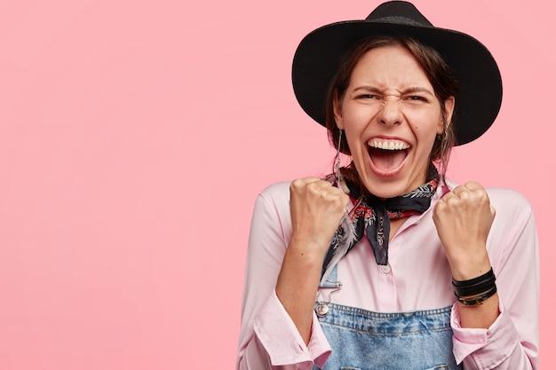 Die aufnahme einer überglücklichen jungen frau hat ein zahniges lächeln, hebt mit erfolg die fäuste, trägt einen hut, hat einen positiven ausdruck und steht an der rosa wand Kostenlose Fotos