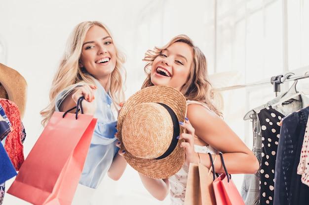 Die beiden jungen hübschen frauen schauen sich kleider an und probieren sie an, während sie im geschäft wählen Kostenlose Fotos