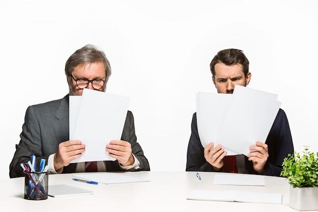 Die beiden kollegen arbeiten im büro zusammen. Kostenlose Fotos