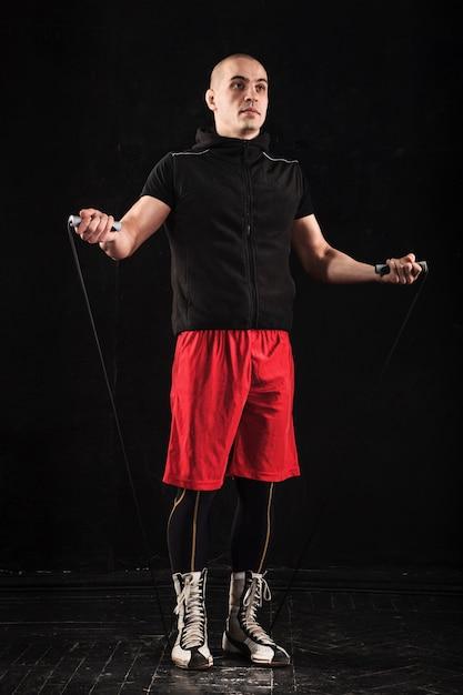 Die beine des muskulösen mannes mit springseiltraining kickboxen auf schwarz Kostenlose Fotos