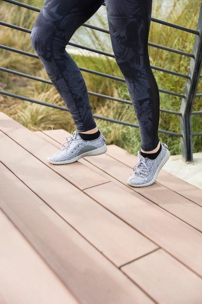 Die beine des weiblichen läuferathleten, der treppe in der städtischen stadt tut herz-sport-training hinaufgeht, laufen während des sommers Premium Fotos