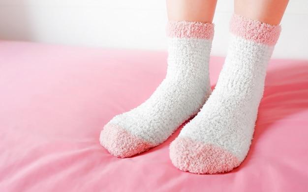 Die beine einer schönen frau tragen warme socken im schlafzimmer. mode rosa socken in gemütlichen. Premium Fotos