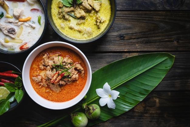 Die bekanntesten thailändischen lebensmittel; rotes curry-schweinefleisch, grünes curry-schweinefleisch, hühnchen-kokos-suppe oder thai in namen Premium Fotos