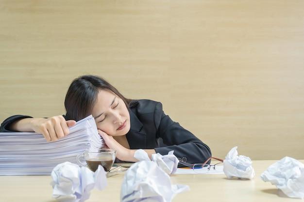 Die berufstätige frau der nahaufnahme, die nachdem sie müde von ihrer arbeit schläft Premium Fotos