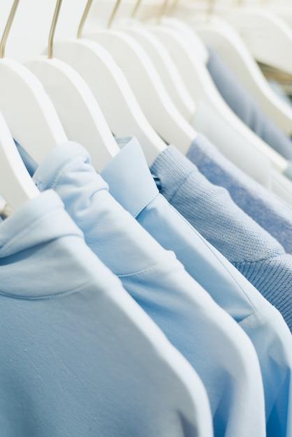 Die blauen sachen der frauen hängen an kleiderbügeln im laden. Premium Fotos