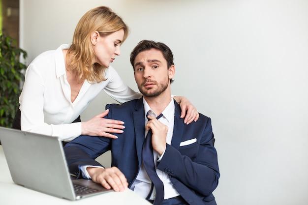 Die blonde chef-geschäftsfrau verführt ihren männlichen assistenten, der mit einem laptop arbeitet Premium Fotos