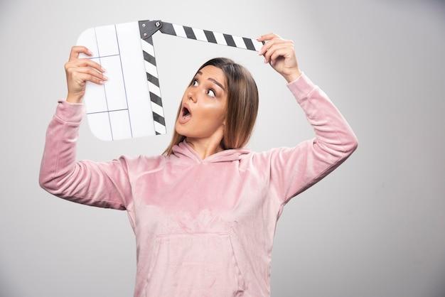 Die blonde dame im rosa sweatshirt mit einer leeren klappe sieht überrascht und verwirrt aus. Kostenlose Fotos