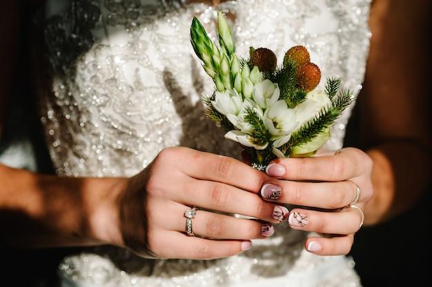 Die braut, die in der hand nahaufnahme des knopflochs des bräutigams weiße blumen und grün und grün hält. vorbereitungen der braut. hochzeit morgen konzept. Premium Fotos