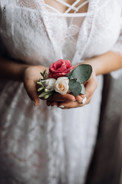 Die braut hält eine butonholle mit rosa und weißen rosen Kostenlose Fotos