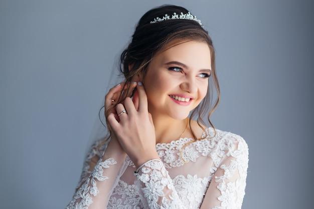 Die braut im hochzeitskleid repariert den ohrring Premium Fotos