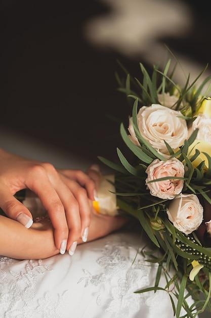 Die braut in einem eleganten durchbrochenen hochzeitskleid hält einen schönen hochzeitsstrauß aus weißen oder beige rosen und grünen blättern. übergibt mädchen mit leichter ordentlicher manikürenahaufnahme. thema hochzeit Premium Fotos