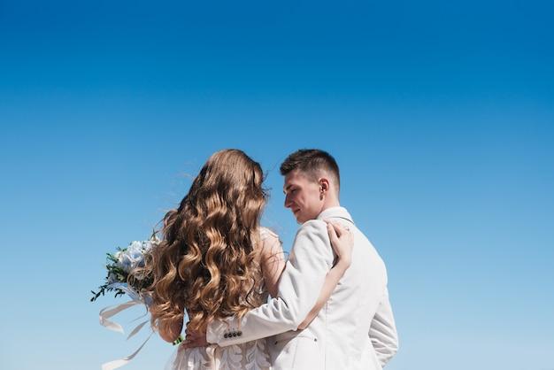 Die braut in einem schönen kleid umarmt den bräutigam in einem leichten anzug gegen den blauen himmel. eine romantische liebesgeschichte. Premium Fotos