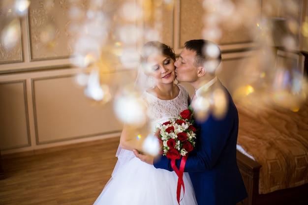 Die braut und der bräutigam, die im hotelzimmer, einen hochzeitsblumenstrauß halten küssen Premium Fotos