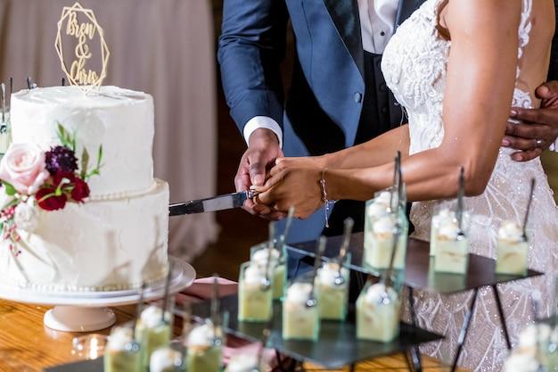 Die braut und der bräutigam schneiden die hochzeitstorte Kostenlose Fotos