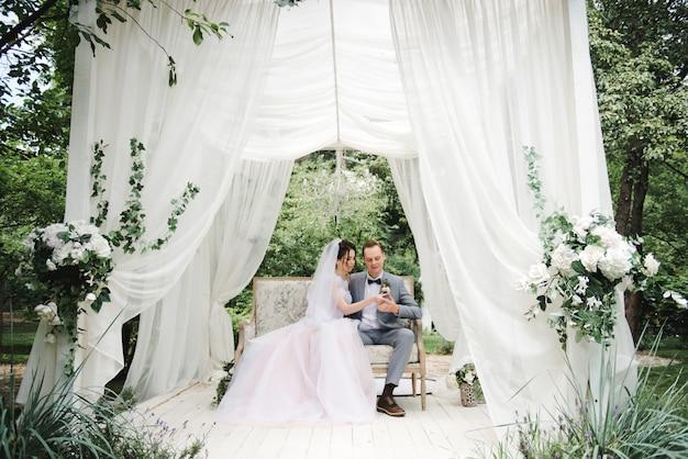 Die braut und der bräutigam sitzen auf einer schönen couch in einem pavillon im garten Premium Fotos