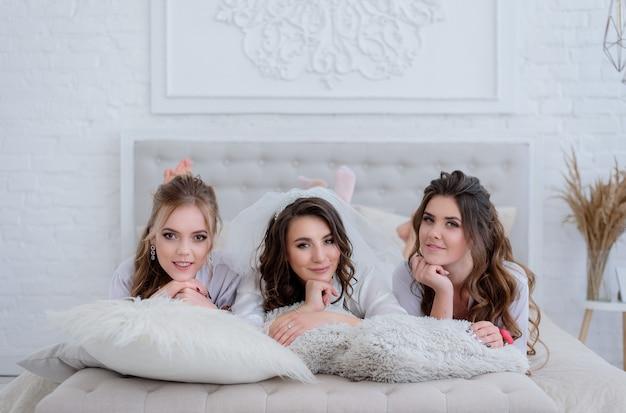 Die braut und zwei attraktive brautjungfern liegen auf dem weißen bett in einem luxuriösen weißen raum Kostenlose Fotos