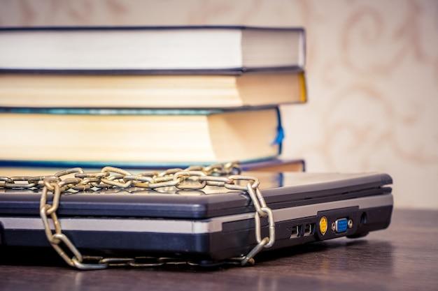 Die bücher liegen auf einem laptop, der durch eine kette verbunden ist Premium Fotos