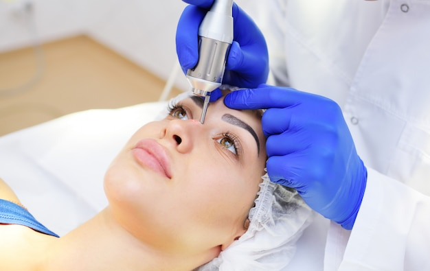 Die chirurgenkosmetikerin entfernt pigmentflecken und gefäßnetze auf der haut des patienten Premium Fotos