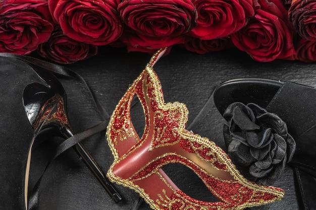 Die colombina, rote karnevals- oder maskerademaske. rosen- und absatzschuhe. Premium Fotos