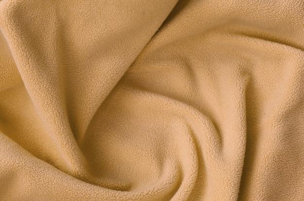 Die decke aus pelzigem orange fleece. ein hintergrund aus hellorangenem weichem plüschfleece mit vielen relieffalten Premium Fotos