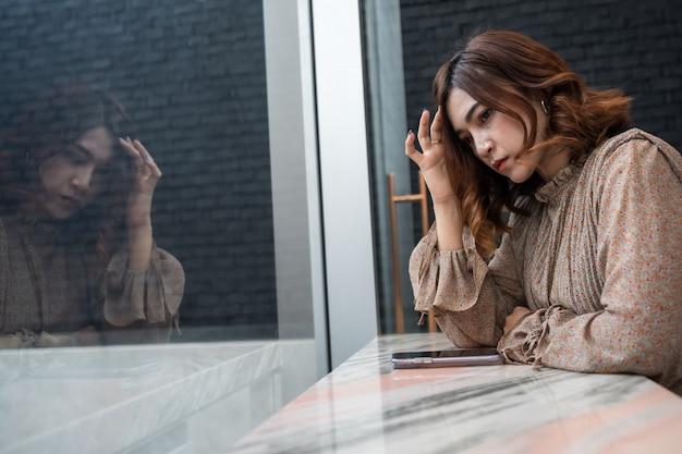 Die deprimierte frau, die kopfschmerzen hat, traurig sich fühlt, sorgen sich um problem Premium Fotos