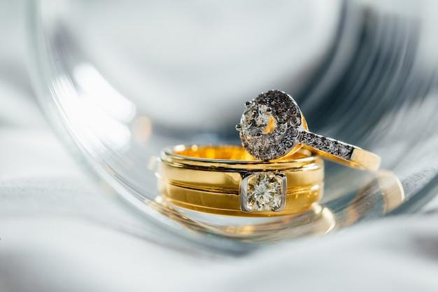 Die diamant-paar-trauringe werden in glas gelegt. Premium Fotos