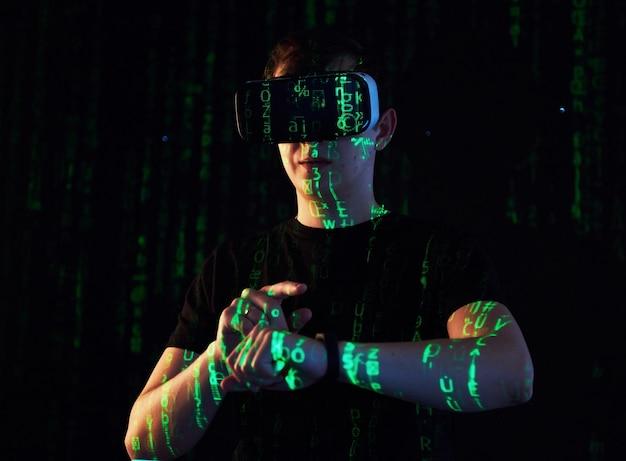 Die doppelbelichtung eines kaukasischen mannes und eines vr-headsets mit virtueller realität ist vermutlich ein spieler oder hacker, der den code in ein sicheres netzwerk oder einen server mit grünen codezeilen knackt Kostenlose Fotos