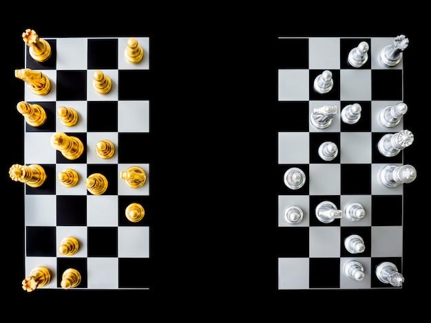 Die draufsicht auf schach und schachbrett ist auf einem schwarzen hintergrund in zwei hälften geteilt. Premium Fotos