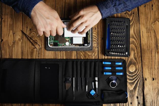 Die draufsicht der hände arbeitet an einem kaputten elektronischen gerät, um es in der nähe der werkzeugtasche und auf dem holztisch im servicegeschäft zu reparieren Kostenlose Fotos