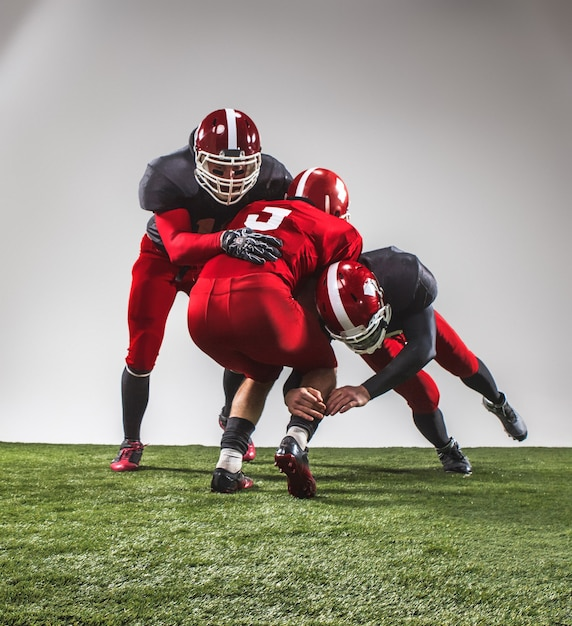 Die drei american-football-spieler in aktion auf grünem gras und grauem hintergrund. Kostenlose Fotos