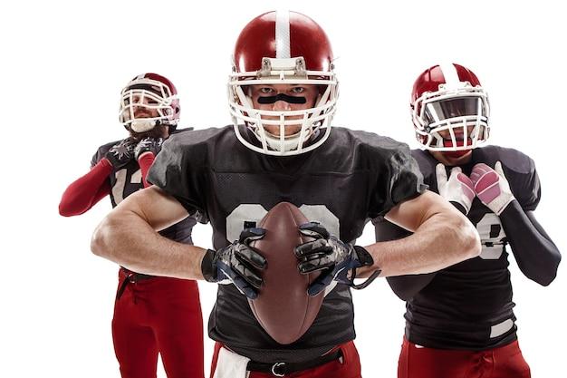 Die drei kaukasischen fitnessmänner als american-football-spieler posieren mit einem ball auf weiß Kostenlose Fotos