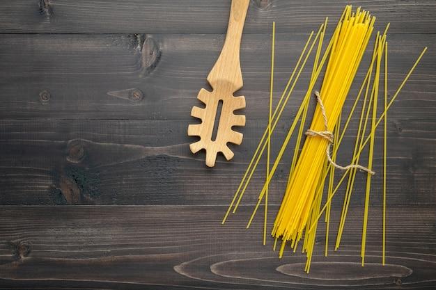 Die dünnen spaghettis auf schwarzem hölzernem hintergrund. Premium Fotos