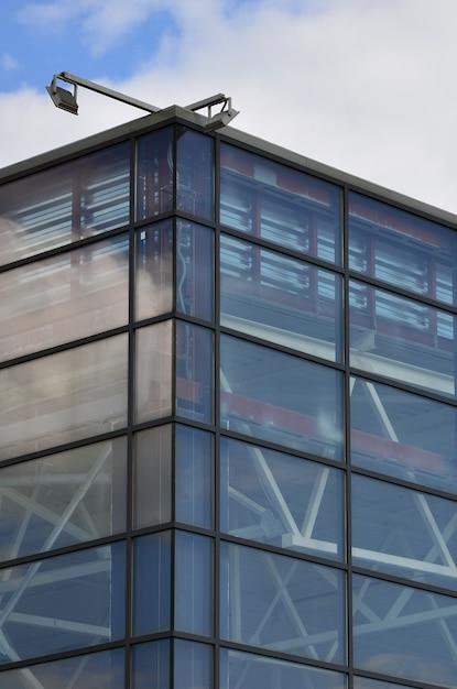 Die ecke des verglasten bürogebäudes mit der eingebauten modernen straßenlaterne Premium Fotos