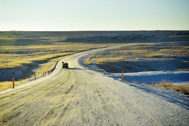 Die eisige kurvige straße mit hintergrund des goldenen sonnenuntergangs im winter in island. Premium Fotos