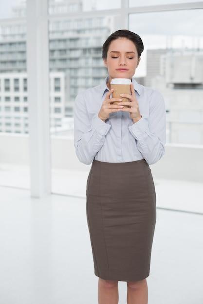 Die elegante geschäftsfrau, die kaffeegeruch mit den augen genießt, schloss im büro Premium Fotos