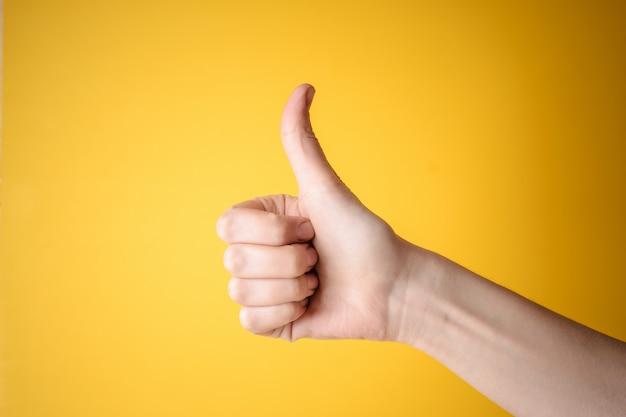 Die emale-hand, die daumen zeigt, up geste Premium Fotos