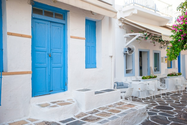 Die engen gassen der insel mit blauen balkonen, treppen und blumen. schönes architekturgebäude außen mit kykladischem stil. Premium Fotos